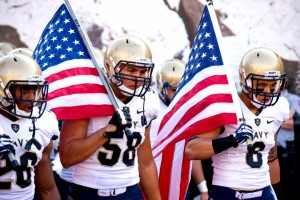 Navy football players marching with the American flag before an Army/Navy game. Photo Credit: AP